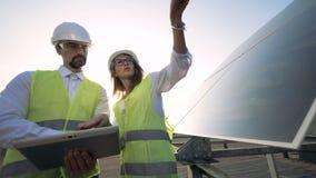 Dwa pracownika sprawdzają panel słoneczny, stoi na dachu, zamykają w górę zdjęcie wideo