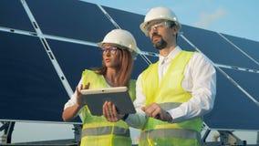 Dwa pracownika stoją blisko panel słoneczny z pastylką zamkniętą w górę zbiory wideo