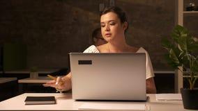 Dwa pracują caucasian kobiety siedzą w brown ceglanym biurze i używają ich laptopy przy białym biurkiem salowym