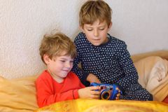Dwa preschool, szkolne dzieciak chłopiec, rodzeństwa lub bracia ma zabawę po dnia powszedniego bawić się gra wideo w domu, i zdjęcia stock