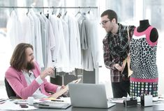 Dwa projektanta mody pracuj? na tworzy? kobiety ` s odzie? w studiu obraz stock
