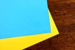 Dwa prześcieradła żółty i błękitny biuro papieru kłamstwo na drewnianym stołowym tle zdjęcie stock