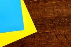 Dwa prześcieradła żółty i błękitny biuro papieru kłamstwo na drewnianym stołowym tle zdjęcie royalty free