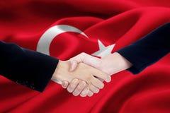 Dwa przedsiębiorców uścisk dłoni z Turcja flaga Obrazy Royalty Free