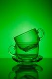 Dwa przejrzystych szklanych filiżanek zielony tło Obraz Stock
