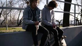 Dwa przyjaciół deskorolkarz i bmx jeździec siedzimy wpólnie na wysokim parapet w miasto łyżwy parka używać ich zbiory wideo
