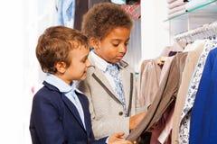 Dwa przyjaciół męski wybierać odziewa w sklepie Obrazy Stock