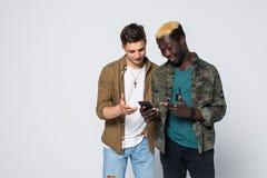 Dwa przyjaciół mieszający biegowy spojrzenie przy adv lub sieci stroną na telefonie odizolowywającym na białym tle zdjęcie royalty free