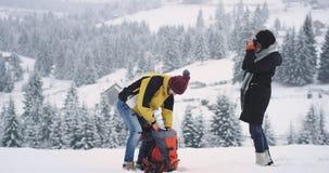 Dwa przyjaciół turysty jeden facet i kobieta przyjeżdżający w zadziwiającym miejscu w wierzchołku pole z śniegiem, przerwę zdjęcie wideo
