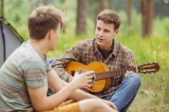 Dwa przyjaciół obsiadanie w namiocie, bawić się gitarę i śpiewa piosenki Fotografia Stock