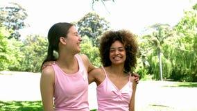 Dwa przyjaciela jest ubranym menchie dla nowotworu piersi w parku zbiory wideo