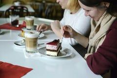 Dwa przyjaciela komunikują z jedzeniem i jedzą tort, napój kawa obrazy royalty free
