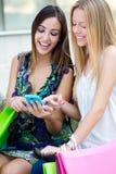 Dwa przyjaciela ma zabawę z smartphones Fotografia Stock