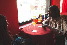 Dwa przyjaciela opowiadają wśrodku baru podczas gdy pijący koktajl zdjęcie stock