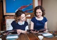 Dwa przyjaciela patrzeje menu w kawiarni Obraz Stock