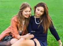 Dwa przyjaciela patrzeje smartphone Fotografia Royalty Free