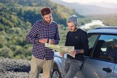 Dwa przyjaciela podróżnika z nakrętką herbaciany znajdować poprawnego sposób i patrzeć papierową mapę Szczęśliwy modnisiów mężczy zdjęcia stock