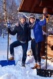 Dwa przyjaciela przeszuflowywa śnieg od jarda w zimy chałupie Obrazy Royalty Free