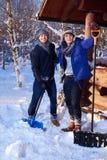 Dwa przyjaciela przeszuflowywa śnieg od jarda w zimy chałupie Obraz Stock