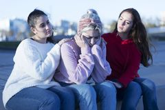 Dwa przyjaciela rozwesela w górę potomstwo przygnębionej dziewczyny outdoors zdjęcia royalty free