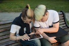 Dwa przyjaciela siedzi na ławce w parku i ogląda pastylkę Zabawę na linii obrazy stock