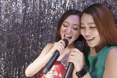 Dwa przyjaciela trzyma mikrofony i śpiew wpólnie przy karaoke Zdjęcie Stock