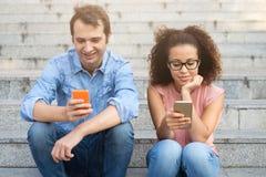 Dwa przyjaciela używa ich telefony komórkowych sadzających Obraz Royalty Free