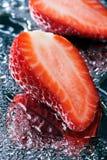 Dwa przyrodniej świeżej truskawki z wodny makro- fotografia stock
