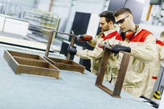 Dwa przystojnego młodego człowieka pracuje w meblarskiej fabryce Zdjęcie Stock