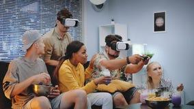 Dwa przystojnej chłopiec bawić się konsoli grę w rzeczywistość wirtualna szkłach wśród rozochoconej firmy zbiory