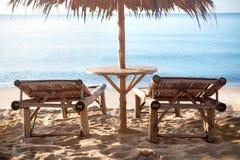 Dwa pustego bambusowego stołu pod słomianym parasolem na białego piaska osamotnionej plaży i loungers, błękitny denny tło fotografia royalty free