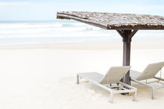 Dwa pustego bryczki longues pod jatą na plaży. Obraz Stock
