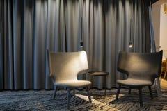 Dwa pustego nowożytny siwieje krzesła z światłami i stołem pośrodku Zasłony na tle obraz royalty free