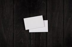 Dwa pustej korporacyjnej tożsamości wizytówki na czarnym eleganckim drewnianym tle, odgórny widok, szablon Obraz Royalty Free