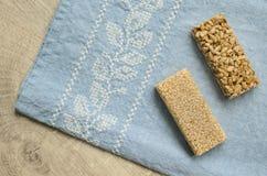 Dwa różnego typ gozinaki bary z słonecznikowymi ziarnami i sezamowymi ziarnami na błękitnym tablecloth tle z broderią na wo Obrazy Royalty Free