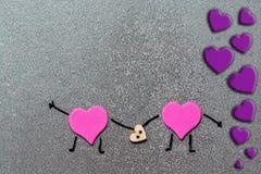 Dwa różowego serca trzymają drewnianego serce w ich rękach Konceptualny wizerunek kochankowie to walentynki dni Zdjęcia Stock