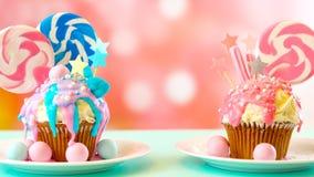 Dwa różowy i błękitne odkrywczość babeczki dekorowali z cukierku i ampuły lizakami obrazy stock