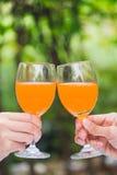 Dwa ręk chwyta szkło sok pomarańczowy obrazy royalty free