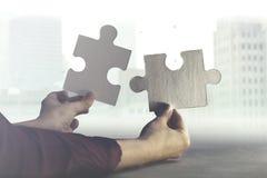 Dwa ręki łączą wpólnie dwa kawałka łamigłówka, pojęcie biznes i drużynowa praca, obrazy royalty free