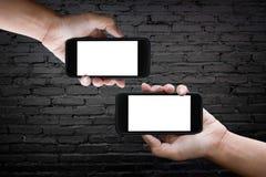 Dwa ręki horyzontalnej trzymający czarnego smartphone z pustego miejsca scr obraz stock