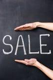 Dwa ręki pokazuje sprzedaż pisać na chalkboard Obrazy Royalty Free