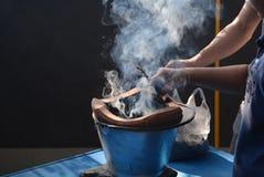 Dwa ręki pomagać rozogniali ogienia w węgiel drzewny kuchence i dymu floa Zdjęcie Stock