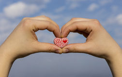 Dwa ręki trzyma czerwonego cętkowanego serce przeciw niebieskiemu niebu Zdjęcia Stock