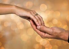 Dwa ręki trzyma each inny z lśnienia światła bokeh tłem Zdjęcie Royalty Free