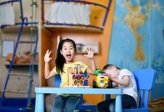 Dwa radosnego dzieciaka chłopiec i dziewczyna bawić się entuzjastycznie przy stołem z zabawkami zdjęcia royalty free