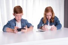 Dwa redhaired dzieciaka bawić się z ich smartphones Obraz Royalty Free