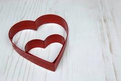 Dwa rewolucjonistek serce Kształtował ciastko krajacza na drewnianym bielu plecy obraz stock
