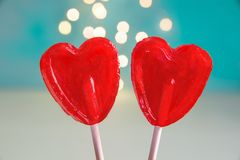 Dwa rewolucjonistka kształta cukierku Kierowego lizaka na kija Turkusowym tle z Błyskać Bokeh światła Walentynki Romantyczna miło Obraz Royalty Free