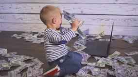 Dwa roczniaka chłopiec z pieniądze i komputerem uśmiechnięty chłopiec obsiadanie przy stołem z laptopu i dolara banknotami Pojęci zbiory wideo