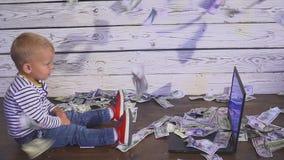 Dwa roczniaka chłopiec z spada pieniądze i komputerem uśmiechnięty chłopiec obsiadanie przy stołem z laptopu i dolara banknotami  zbiory